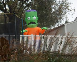 A blow up Frankenstein monster in a back yard.